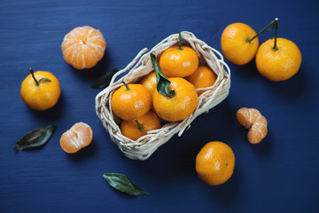 Tangerines with green leaves in a wicker tray, studio shot