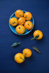 Above view of ripe mandarins in a saucer, vertical shot