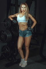 Skinny girl is standing in a gym.