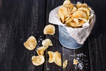 Homemade potato chips over dark wooden background