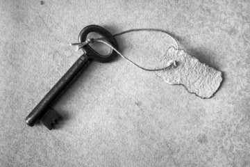 Old key with slip of paper on rustic paper, monochrome