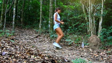 sporty woman running in jungle forest and drinking water. HD.