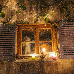 Flockenwirbel vor weihnachtlichem Fenster