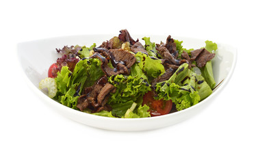 Salad with meat in white bowl isolated