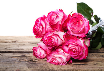 Pink fresh roses on wood