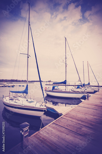 Retro filtered picture of yachts at pier.