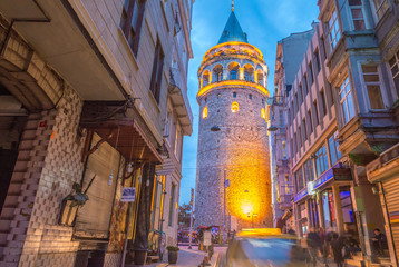 Beautiful sunset view of Galata Tower framed by street buildings