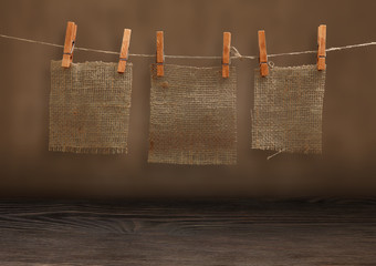 pieces of burlap hanging on clothespins in grunge room