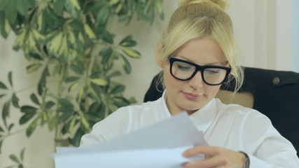 Close up of a business woman discontentedly checking documents