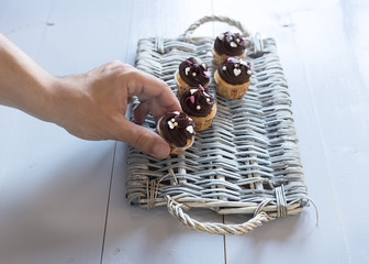Hand putting a delicious chocolate cupcakes on a wicker tray