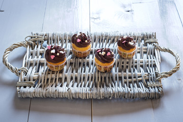 Four delicious chocolate cupcakes on a wicker tray