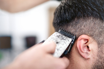 men's hairstyling and haircutting with hair clipper in a barber