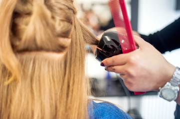 Blonde woman at hair salon using a professional tool