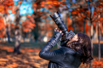 brunette young woman photographer taking pictures in autumn