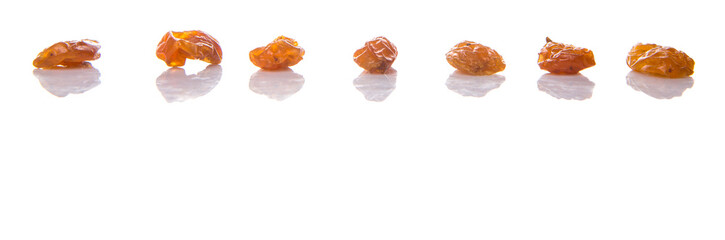 Dried orange colored raisin over white background