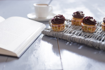 Reading is a pleasure. Four chocolate cupcakes and a open book