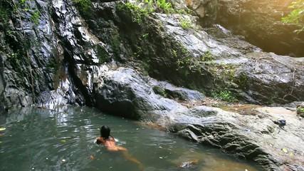 Nude sexy woman swims in a pond near waterfall. HD. 1920x1080