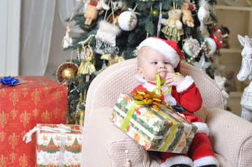 Kid in Santa Claus costume opening a present