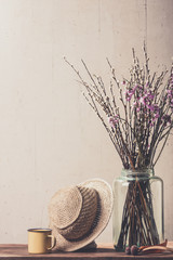 Dry flowers in a vase and vintage hat
