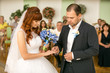 handsome groom putting wedding ring on brides hand at registry o