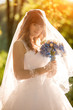 redhead bride standing in beam of light and holding bouquet unde