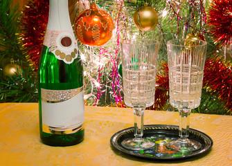 Christmas holiday, wine and glasses near a Christmas fir-tree.