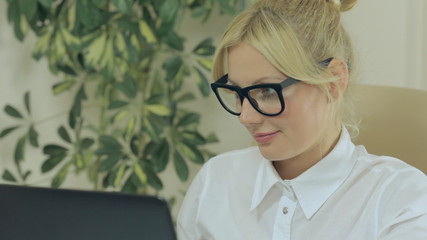 Attractive blonde woman looking at the monitor screen