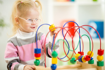 Kid in eyeglases playing colorful toy in home interior