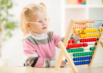 Funny kid in eyeglases counting using abacus