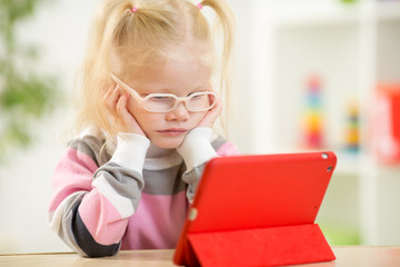 happy child in glasses looking at mini tablet pc screen