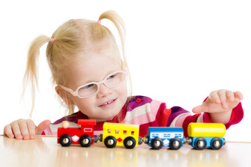 Kid in eyeglases playing toy train isolated