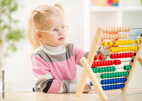 canvas print picture Funny kid in eyeglases counting using abacus