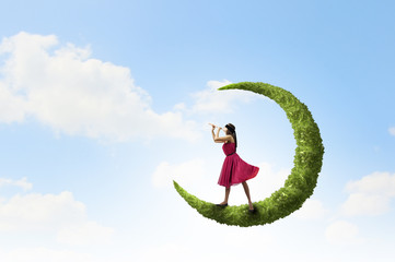 Woman standing on green moon