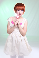 Girl with red hair with lollipop in white dress on light