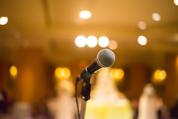 microphone in concert hall or conference room with warm lights i