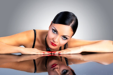 Beautiful black hair woman, laying on top of reflective table.