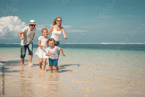 Leinwanddruck Bild Happy family running on the beach at the day time