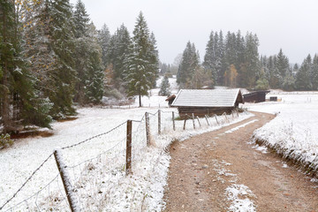 countryside road and wooden hut in winter