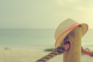 Forgotten straw hat against sea background.