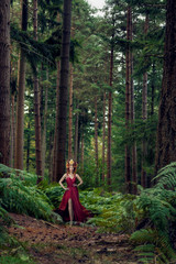 Beautiful woman in forest with deers