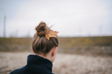 the girl during the autumn period with a maple leaf in hair