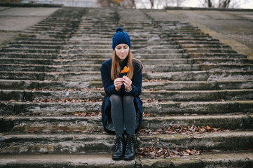 the girl in a blue cap sits on steps