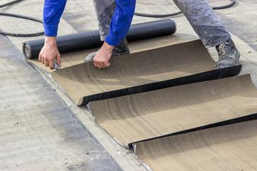 Insulation worker cutting insulation bitumen material rolls