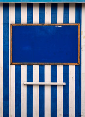 Tattered seaside blue white notice board, beach hut