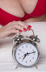 Woman's hand and an alarm clock