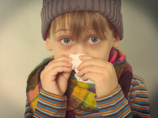 ill boy wiping his nose