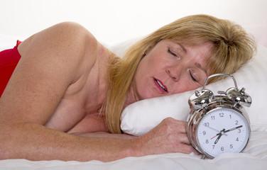 Woman fast asleep with alarm clock
