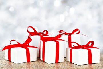 Group of white and red gift boxes over a twinkling background