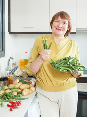 woman with okra in domestic kitchen