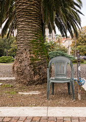 Anti theft device - chair padlocked to post. Under palm tree.